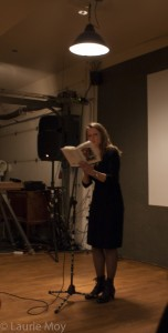 woman in dark room, reading from a book
